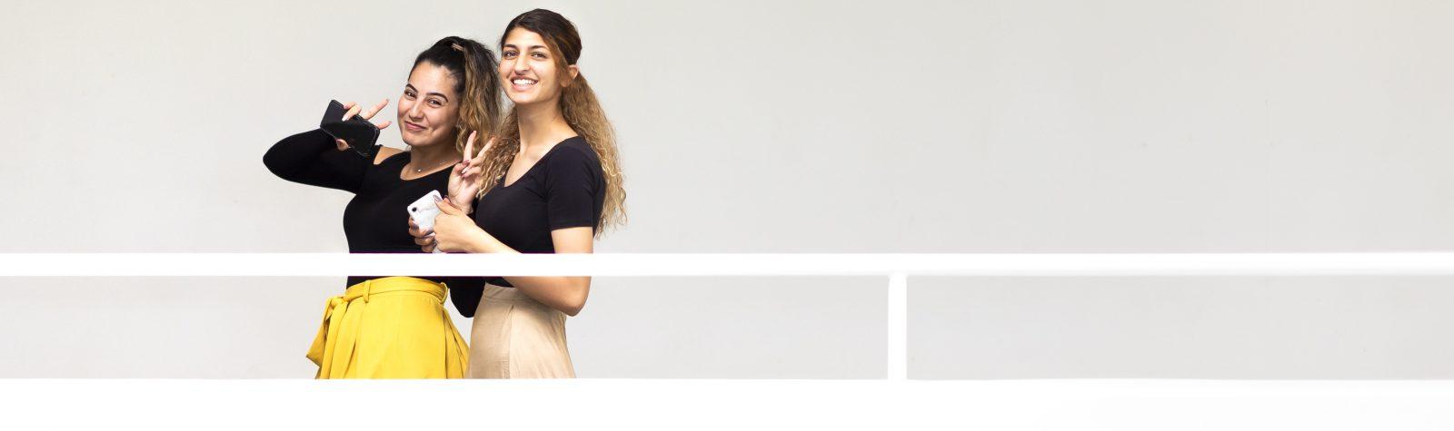 To elever smiler til fotografen fra den anden side af gangen