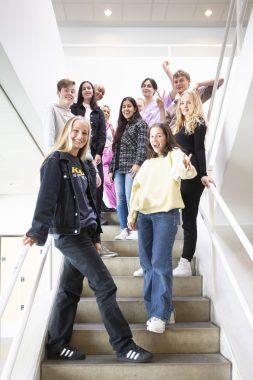 En gruppe elever poserer på trappen indenfor på HTG