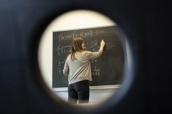 Matematiklærer Sara skriver formler på tavlen